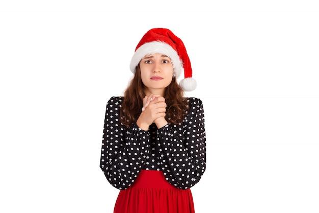 Sombre femme mignonne et timide en robe tenant par la main dans la prière, demandant des excuses ou aide, fille émotive au chapeau de père noël isolé sur blanc,