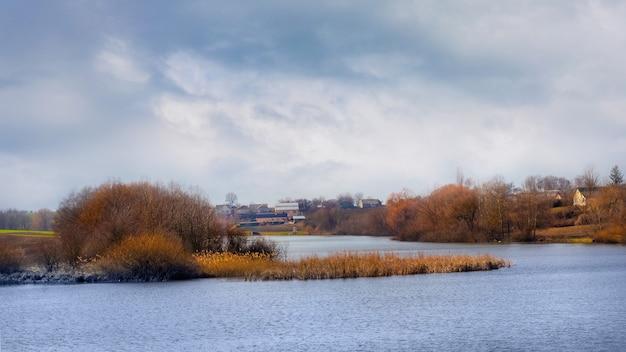 Sombre journée d'automne. nuages gris foncé sur la rivière en automne