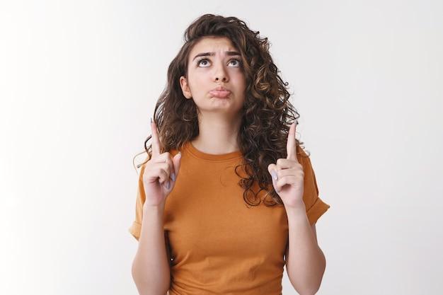 Sombre mignon triste jeune fille aux cheveux bouclés espoir arménien pinçant les lèvres levant les lèvres parlantes demandant de l'aide pour réaliser le vœu croiser les doigts bonne chance très contrarié debout fond blanc suppliant