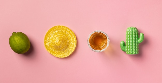 Sombrero, citron vert, tequila et cactus sur fond rose.