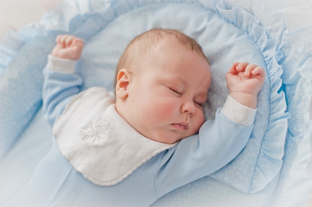 Le sommeil réparateur de bébé. nouveau-né dans un berceau en bois. le bébé dort dans le berceau de chevet.