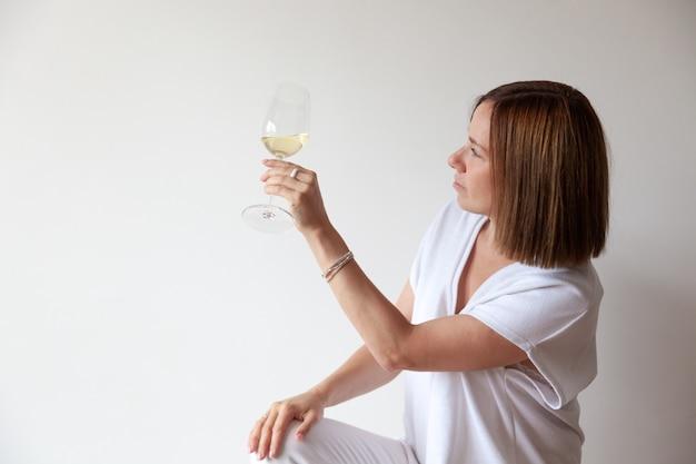 Sommelier fille brune caucasienne tenant un verre de vin blanc