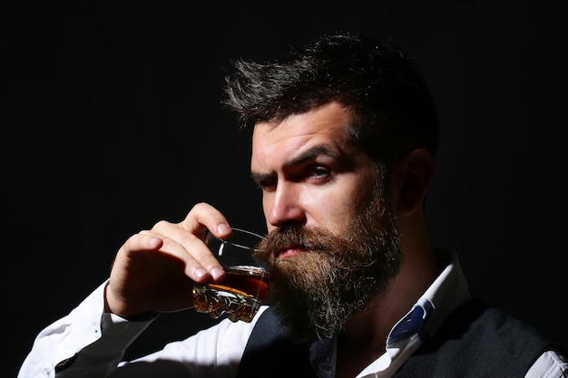 Le sommelier goûte une boisson chère. homme d'affaires barbu en costume élégant avec verre de cognac. concept de dégustation et de dégustation de vin.