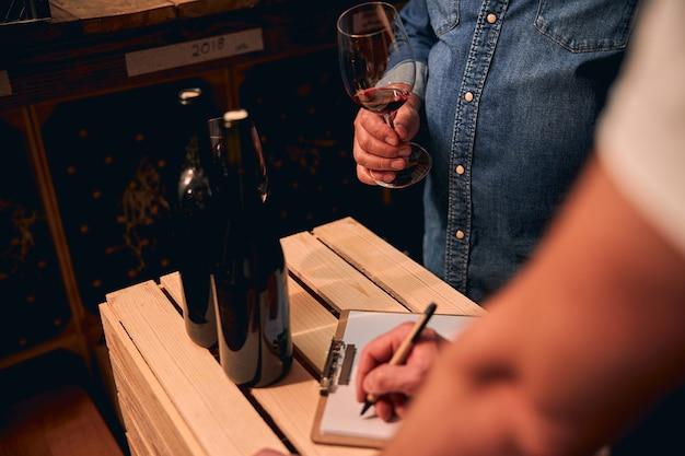 Sommelier masculin non reconnu debout dans la cave avec un verre de vin rouge pendant que son assistant prend des notes