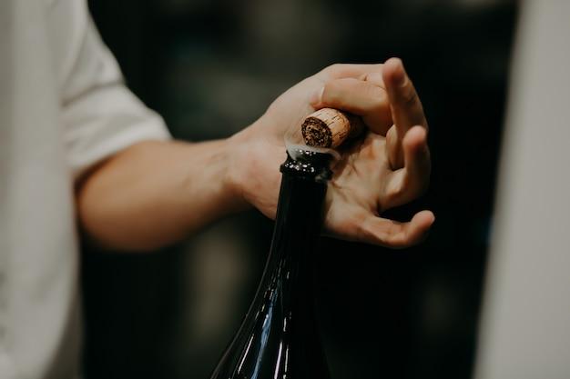 Sommelier ouvrant une bouteille de vin dans la cave à vin