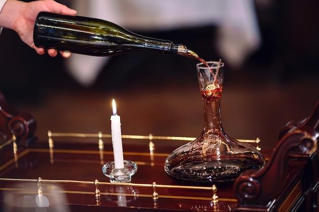 Un sommelier versant du vin rouge dans une carafe