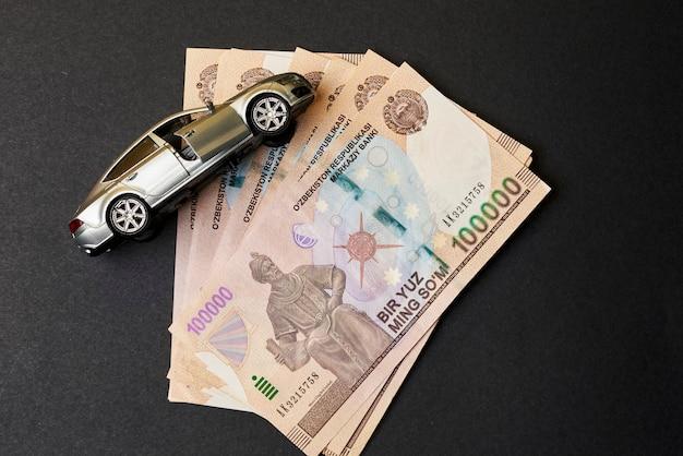 Sommes ouzbeks et jouet de voiture concept d'assurance automobile en ouzbékistan