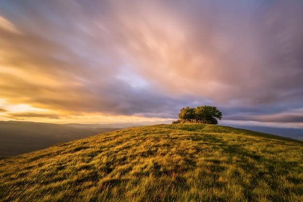 Le sommet du mont pratomagno en toscane au coucher du soleil (italie). une montagne particulière dont le sommet est constitué par une grande pelouse avec peu de végétation.