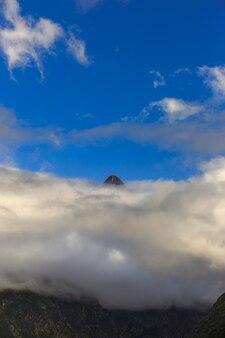 Sommet de la montagne au-dessus des nuages contre le ciel bleu