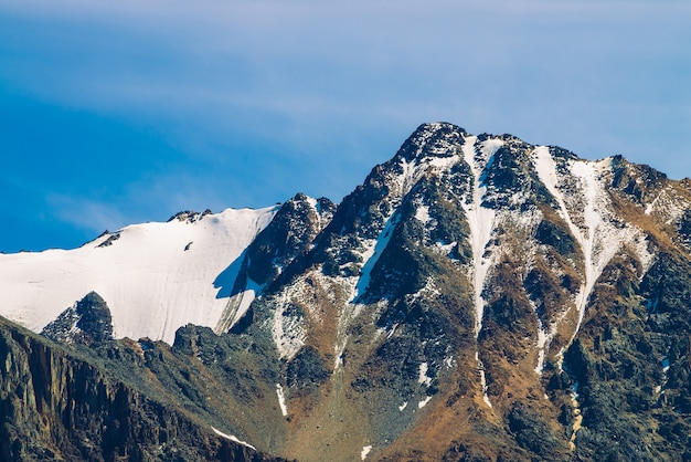 Sommet de la montagne enneigée dans un ciel bleu clair. crête rocheuse sous les nuages en journée ensoleillée. paysage minimaliste atmosphérique de nature majestueuse.