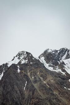 Sommet de la montagne enneigée dans le ciel bleu clair. crête rocheuse sous les nuages en journée ensoleillée.