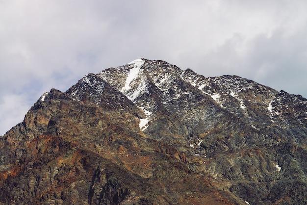 Sommet de la montagne enneigée dans le ciel nuageux