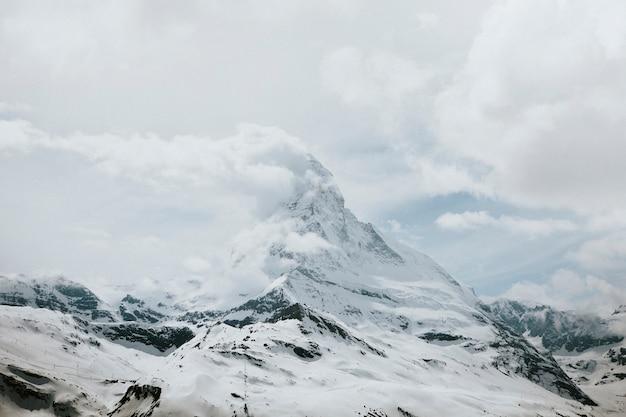Sommet de la montagne enneigée par temps nuageux
