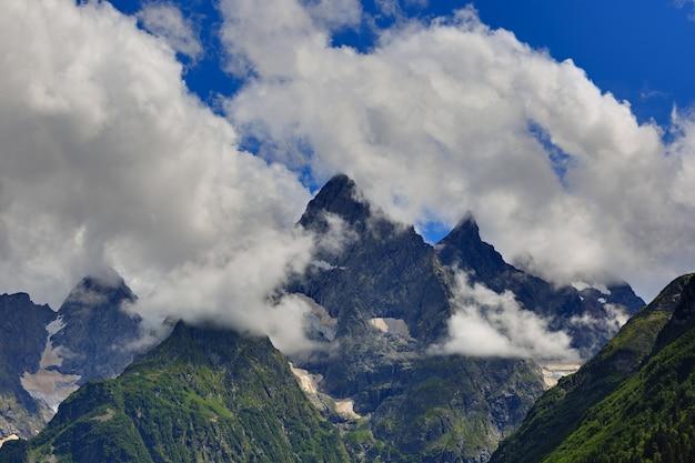 Sommet de la montagne avec des glaciers sur fond de nuages et de ciel