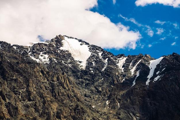 Sommet de la montagne rocheuse enneigée sous un ciel bleu nuageux