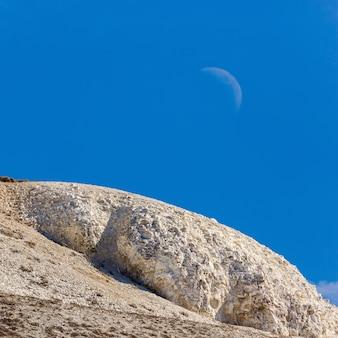 Le sommet des montagnes de craie contre un ciel clair avec la lune.