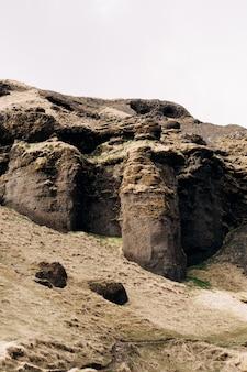 Le sommet des montagnes rocheuses en islande le pied de la montagne est recouvert d'herbe jaune
