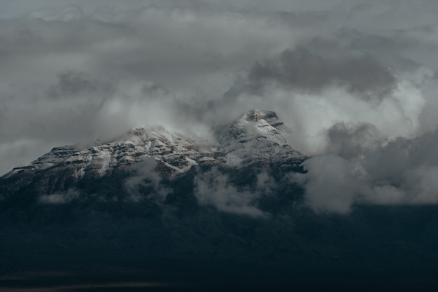 Sommets enneigés des montagnes couvertes par le ciel nuageux sombre