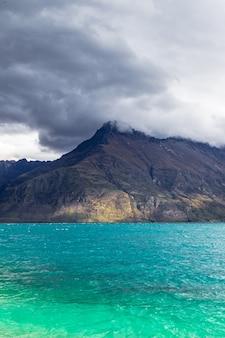 Les sommets des montagnes jusqu'aux nuages sur l'eau turquoise jour de pluie au lac wakatipu nouvelle-zélande
