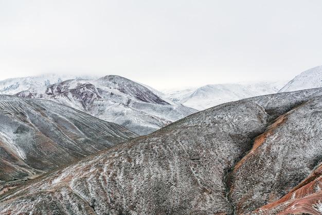 Les sommets des montagnes rouges sont couverts de neige, paysage hivernal des hautes terres