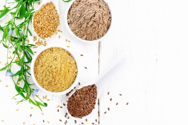 Son de lin et farine dans deux bols, graines dans des cuillères, feuilles de lin et fleurs sur fond de planche de bois d'en haut
