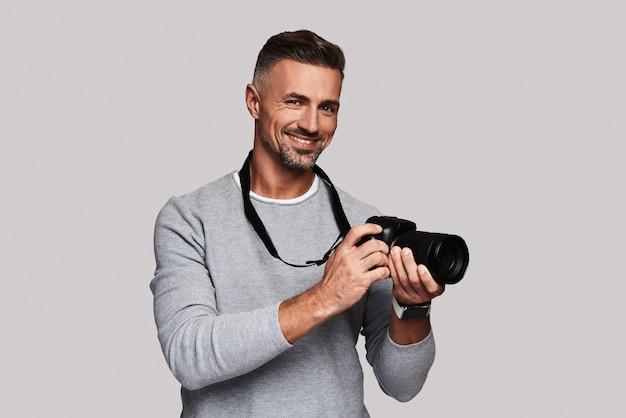 Son meilleur passe-temps. beau jeune homme tenant un appareil photo numérique et souriant en se tenant debout sur fond gris