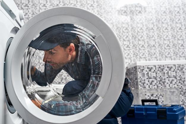 Son plombier facile à travailler dans la salle de bain vérifiant la machine à laver