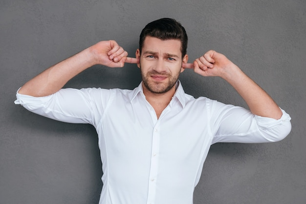 Son trop fort ! jeune homme frustré couvrant les oreilles avec les mains et