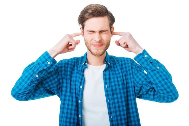 Son trop fort ! jeune homme frustré tenant les doigts dans ses oreilles et gardant les yeux fermés