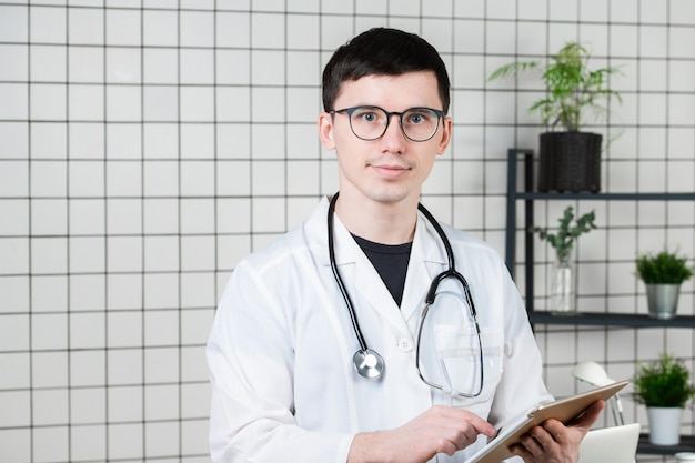 Songeur beau jeune médecin de sexe masculin à l'aide de la tablette tactile.