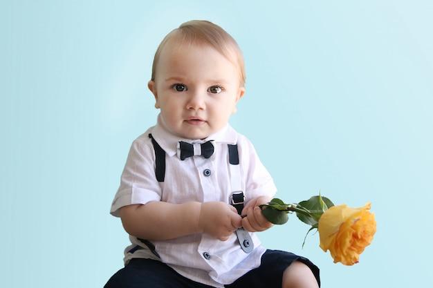 Songeur petit garçon dans une chemise blanche avec un noeud papillon tenant une rose jaune