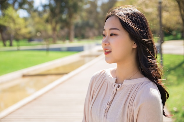 Songeuse asiatique fille appréciant le paysage dans le parc de la ville