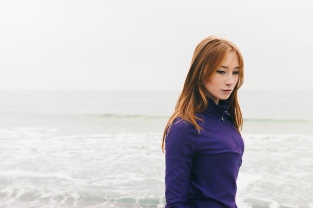 Songeuse belle jeune fille rousse sur la plage par temps nuageux