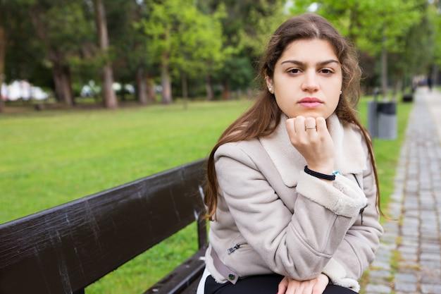 Songeuse fille latine attend quelqu'un dans le parc