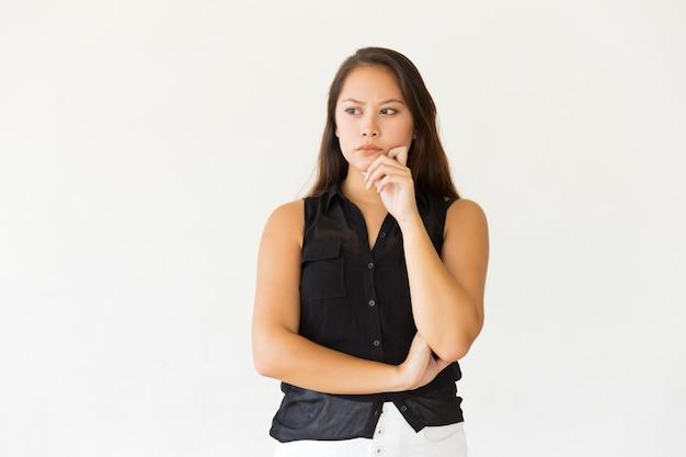 Songeuse jeune femme avec la main sur le menton