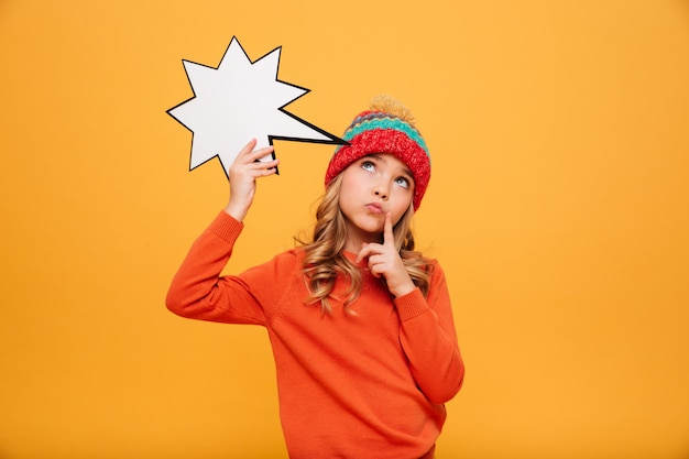 Songeuse jeune fille en pull et chapeau tenant une étoile de discours vide et levant sur orange