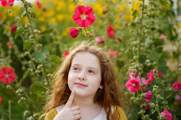 Songeuse petite fille touchant le menton avec le visage de l'expression de la pensée.