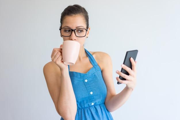 Songeuse séduisante jeune femme à lunettes, boire du café et à l'aide de smartphone.