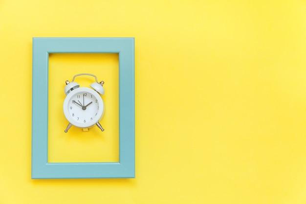 Sonnerie double réveil vintage dans un cadre bleu isolé sur fond tendance coloré jaune