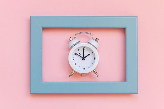 Sonnerie double réveil vintage dans un cadre bleu isolé sur fond tendance coloré pastel rose