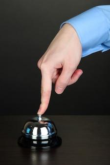 Sonnerie à la main en cloche de service sur table en bois sur fond noir