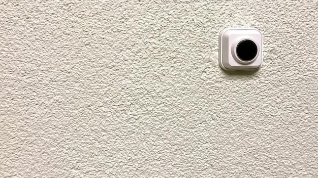 Sonnette en plastique avec bouton noir sur mur texturé blanc. bouton en plastique sur mur plâtré. bouton rond à presser. espace auteur. grand espace de fond pour une inscription ou un logo