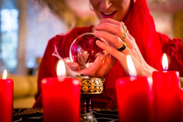 Soothsayer in seance avec boule de cristal et fumée