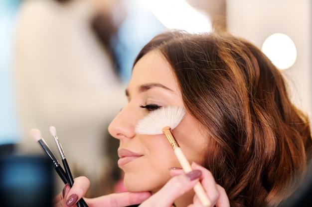 Sophistiquée belle brune caucasienne assise dans un salon de beauté pendant que la maquilleuse met un fard à joues sur les joues de la femme.