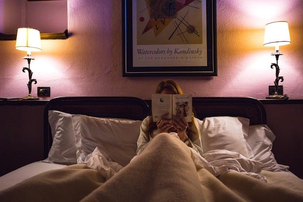 Sorano, italie - 7 avril 2017 : la vue de la jeune fille est allongée dans son lit à l'hôtel et lit un livre. sorano, italie - 7 avril 2017