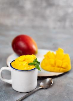 Sorbet à la mangue dans une tasse blanche sur fond gris