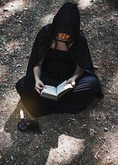 Un sorcier tenant un livre ouvert et assis sur un terrain forestier