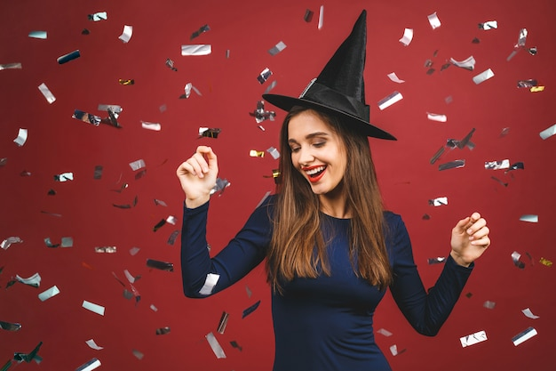 Sorcière au maquillage brillant et aux cheveux longs. belle jeune femme surprise posant en costume sexy de sorcières. isolé sur fond rouge avec des confettis.