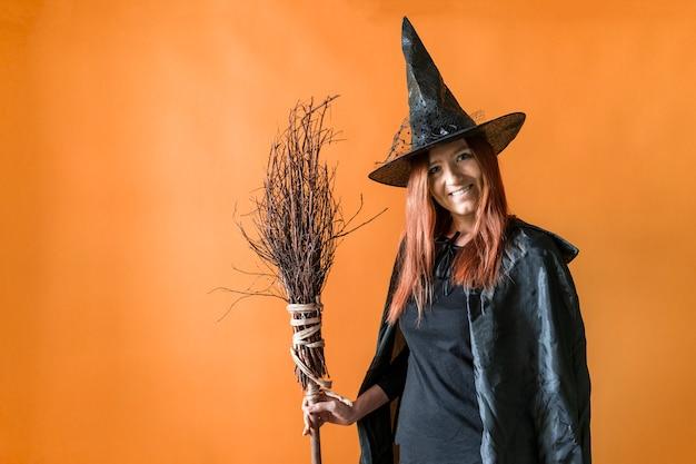 Une sorcière aux cheveux rouges sourit et tient un balai