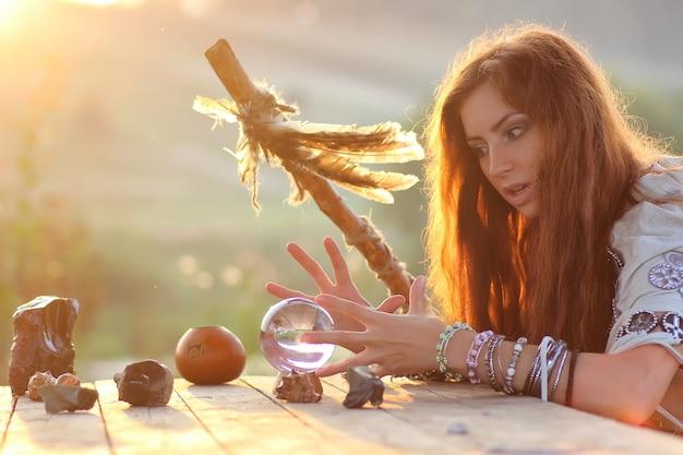 Sorcière avec boule de cristal au coucher du soleil